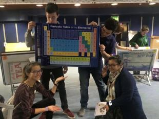 group photo from an EngPals session with four students holding a Periodic table of elements